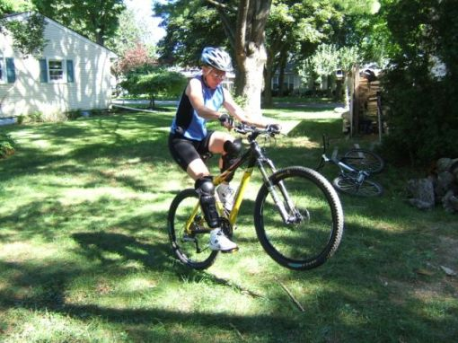 Terri with good backyard wheelie form, arms extended and torso vertical